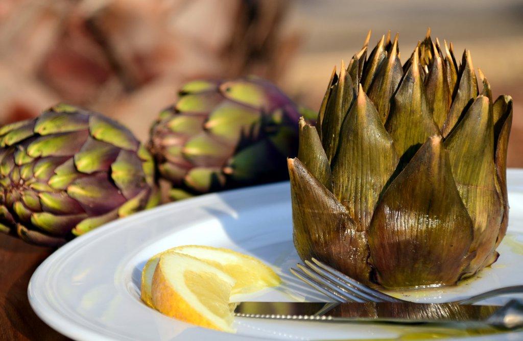 Zeytinyağlı enginar yemeği tabakta dilim limon ile servis edilmiş