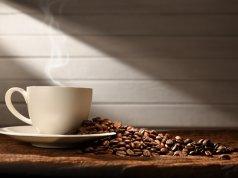 bir fincan kahve ve tabağına saçılmış kahve çekirdekleri