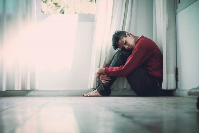 yorgunluk hisseden delikanlı dizlerini karnına çekmiş yerde oturuyor.
