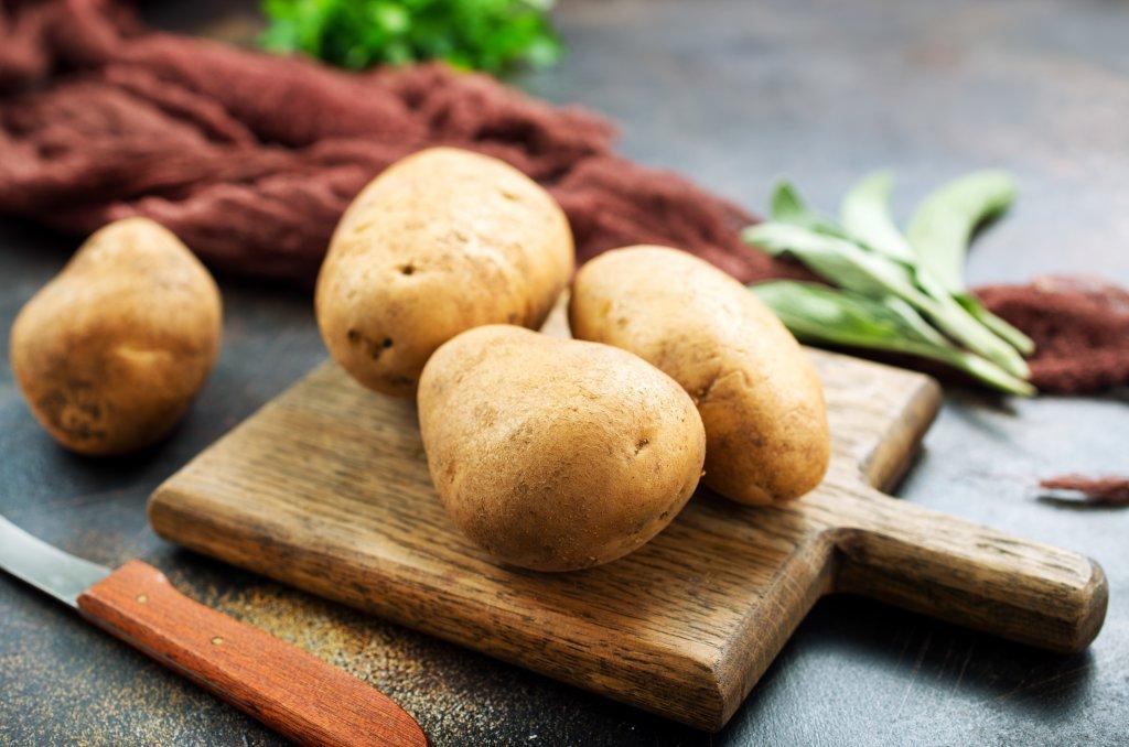 kesme tahtası üstüne yerleştirilmiş patates resmi