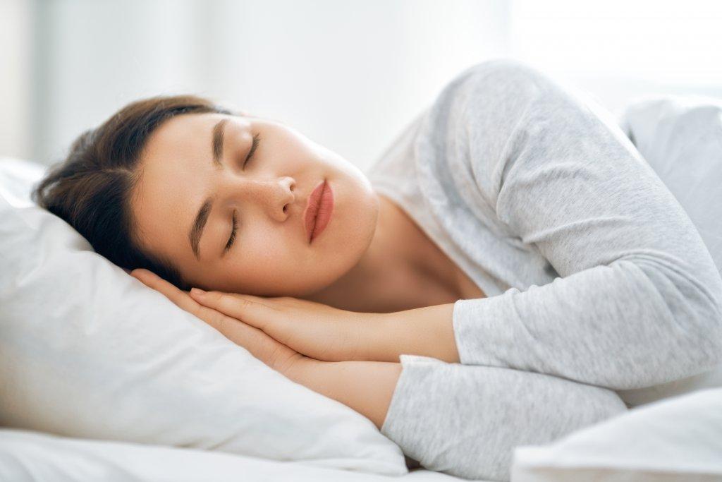 beyaz arkaplan önünde yatağa yatmış uyuyan bayan resmi