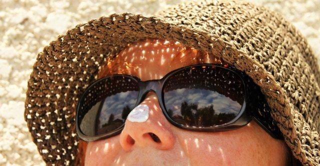 Güneşten korunma şapkası takan bayanın burnunda güneş kremi var