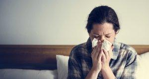 Alerjik problemler yaşayan bayan yatakta oturuyor