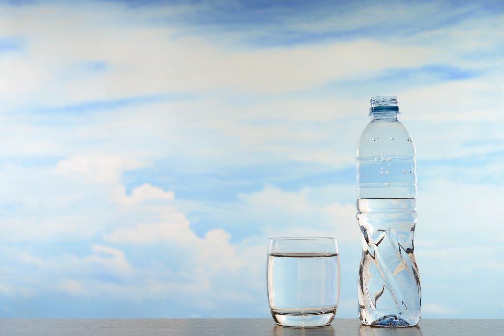 mavi gökyüzünün önünde bir şişe ve bardak su